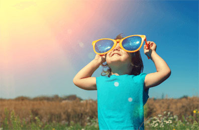 child wearing sunglasses looking at the sun